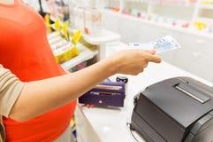 有金钱的孕妇在钱柜在药房 免版税图库摄影