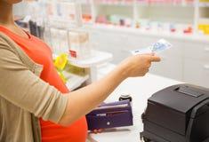 有金钱的孕妇在钱柜在药房 图库摄影