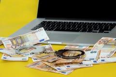 有金钱的手铐在膝上型计算机键盘 库存图片