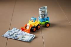 有金钱的玩具拖拉机在桌上 库存图片