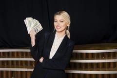 有金钱的美丽的白肤金发的女实业家在黑衣服的顶楼办公室 库存图片