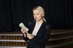 有金钱的美丽的白肤金发的女实业家在黑衣服的顶楼办公室 免版税库存照片
