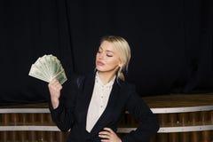 有金钱的美丽的白肤金发的女实业家在黑衣服的顶楼办公室 库存照片