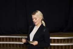 有金钱的美丽的白肤金发的女实业家在黑衣服的顶楼办公室 免版税库存图片