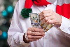 有金钱的老人在圣诞节背景 免版税库存照片