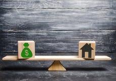 有金钱的议院在等级和木块 房地产购买的概念 物产销售  抵押的付款 免版税库存图片