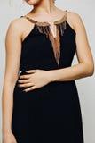 有金首饰的典雅的时兴的黑礼服在与卷曲长白肤金发的一个美好的年轻白肤金发的女孩时装模特儿 库存图片