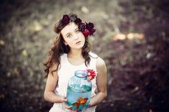 有金鱼的年轻美丽的女孩 库存照片