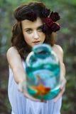 有金鱼的年轻美丽的女孩 库存图片