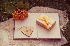 有金黄丝带、心脏和一本开放书的礼物盒在绿草 秋天概念查出的白色 仍然秋天明亮的礼品寿命 免版税库存图片