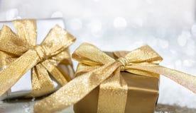 有金黄丝带的圣诞礼物箱子在抽象bokeh光和闪烁背景 库存图片