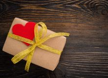 有金黄丝带的礼物盒和在木纹理黑暗的红色心脏 免版税库存照片