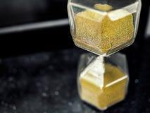 有金黄沙子种子的现代六角形滴漏 图库摄影