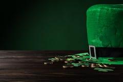 有金黄硬币的绿色在木桌上的帽子和三叶草 库存照片
