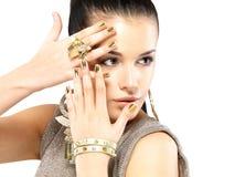 有金黄钉子和美丽的金珠宝的妇女 免版税图库摄影