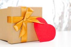 有金黄丝带和红色心脏的礼物盒在银色闪烁的背景的一张白色桌上说谎 库存照片