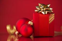 有金黄丝带和xmas中看不中用的物品的红色礼物盒在红色背景 免版税库存图片