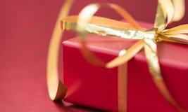 有金黄丝带的红色礼物盒在红色背景 免版税库存图片