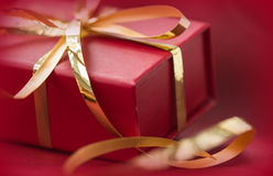 有金黄丝带的红色礼物盒在红色背景 库存图片
