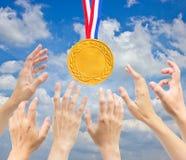 有金黄奖牌的手。 免版税库存图片