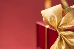 有金黄弓的礼物盒在红色背景 免版税库存图片