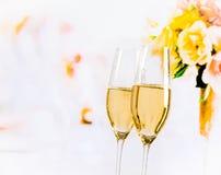 有金黄泡影的香槟槽在婚礼开花背景 免版税库存图片