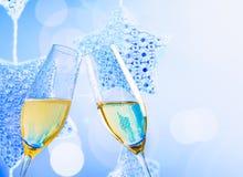 有金黄泡影的香槟槽在蓝色圣诞灯装饰背景 免版税库存照片