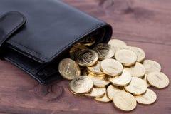 有金黄硬币的黑皮革钱包在木背景 免版税库存照片