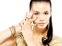 有金黄钉子和美丽的金首饰的妇女 免版税库存照片