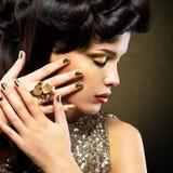 有金黄钉子的美丽的妇女 库存图片