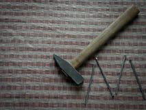 有钉子的锤子在棕色木桌上 库存照片