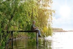有钓鱼竿传染性的鱼的人 免版税库存照片