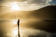 有钓鱼竿持有人的渔夫在原野的日落期间是 库存图片