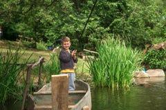 有钓鱼竿渔的男孩在一条木小船 免版税库存图片