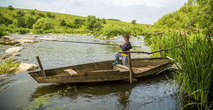 有钓鱼竿渔的男孩在一条木小船 库存照片