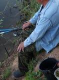 有钓鱼竿的人在池塘 库存图片