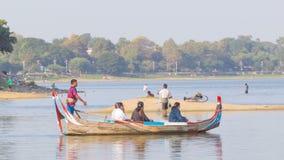 有钓鱼竿立场的人在Taungthaman湖中水  免版税库存图片