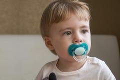 有钝汉的婴孩在他的嘴坐床在屋子里 免版税图库摄影