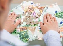 有钞票和硬币的买卖人 免版税图库摄影