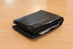有钞票的黑皮革钱包背景木头的人的 免版税库存照片