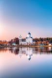 有钟楼的亚历山大・涅夫斯基正统湖岸的基督教会和教堂在日落 图库摄影