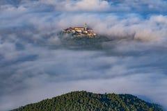 有钟楼的在云彩上的古镇布泽特和飞行 库存图片