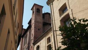 有钟楼的老教会在房子和一棵植物之间在帕尔瓦,意大利 股票录像