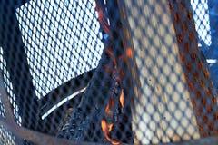 有钢格栅的室外烟囱和木柴在灼烧的过程中 免版税库存照片
