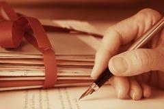 有钢笔文字的葡萄酒古色古香的手在特写镜头上写字 免版税库存图片