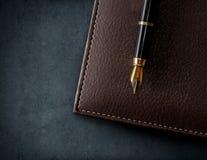有钢笔的皮革棕色笔记本 库存照片