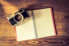 有钢笔的空白的笔记本和在木的减速火箭的照相机 库存照片