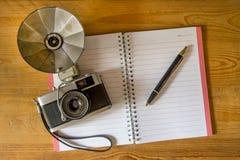 有钢笔的空白的笔记本和在木的减速火箭的照相机 免版税库存照片