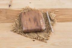 有钢笔的老钱包在木背景 免版税库存照片