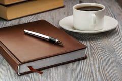 有钢笔的闭合的笔记本在土气桌上 在笔记本的笔 免版税库存照片